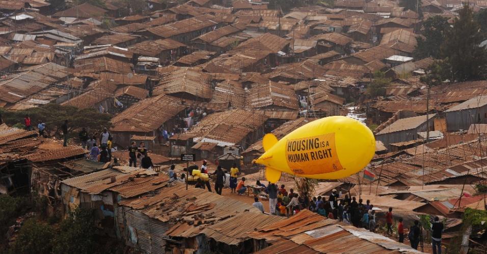 """Membros da ONG Anistia Internacional voam em balão de ar quente por meio da favela Kibera, em Nairobi, no Quênia, para chamar atenção ao problema de habitação no país. O cartaz preso ao balão diz: """"Moradia é um direito humano"""""""