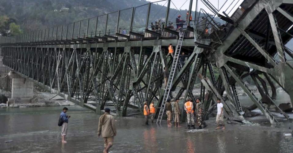 Equipes de resgate socorrem feridos após o desabamento de ponte ainda em construção, localizada sobre rio perto de Srinagar Alaknanda, no estado indiano de Uttarakhand, neste domingo (25)