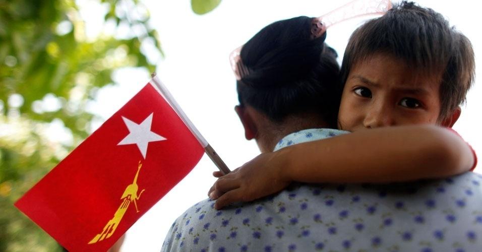 Garoto segura bandeira da Liga Nacional para Democracia em comício de campanha eleitoral realizado neste domingo (25), em Mianmar