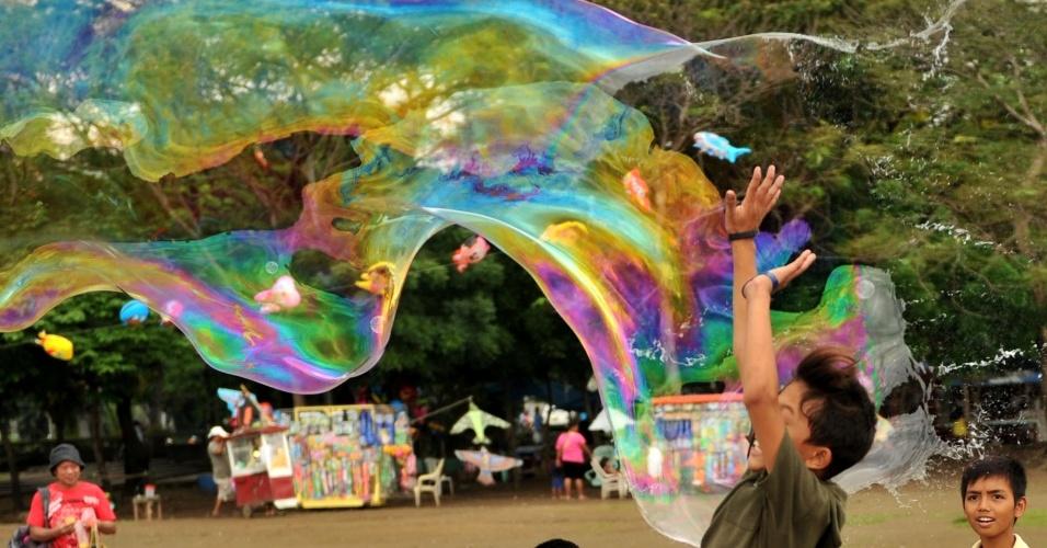 Garoto tenta estourar bolha de sabão gigante feita com uma solução de fórmula secreta, no parque Luneta, em Manila, nas Filipinas