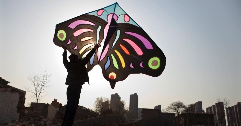 Homem segura pipa em formato de uma borboleta enquanto espera pelo vento, na área residencial de Shijiazhuang, na província de Hebei, na China