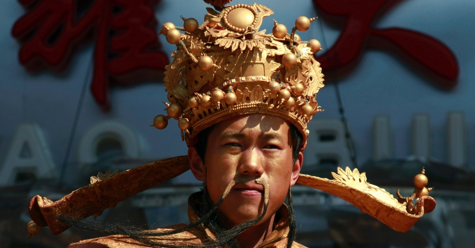"""Homem vestido com fantasia de """"deus da prosperidade"""" distribui envelopes vermelhos em shopping de bairro de Pequim, na China"""
