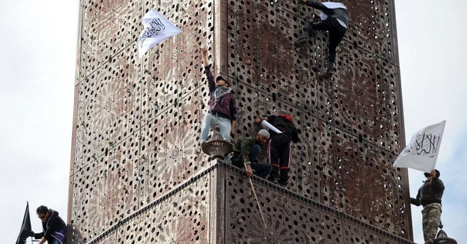 Salafistas balançam bandeira na torre do relógio durante manifestação neste domingo (25) em Tunis, capital da Tunísia. Milhares de salafistas pedem aplicação da lei islâmica na nova Constituição