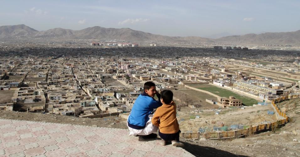 Garotos afegãos conversam com a vista de Cabul, capital do Afeganistão, embaixo deles