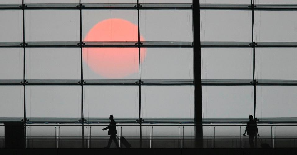 Passageiros andam com sua bagagem no Hongqiao Shanghai Railway Station durante pôr do sol em Xangai