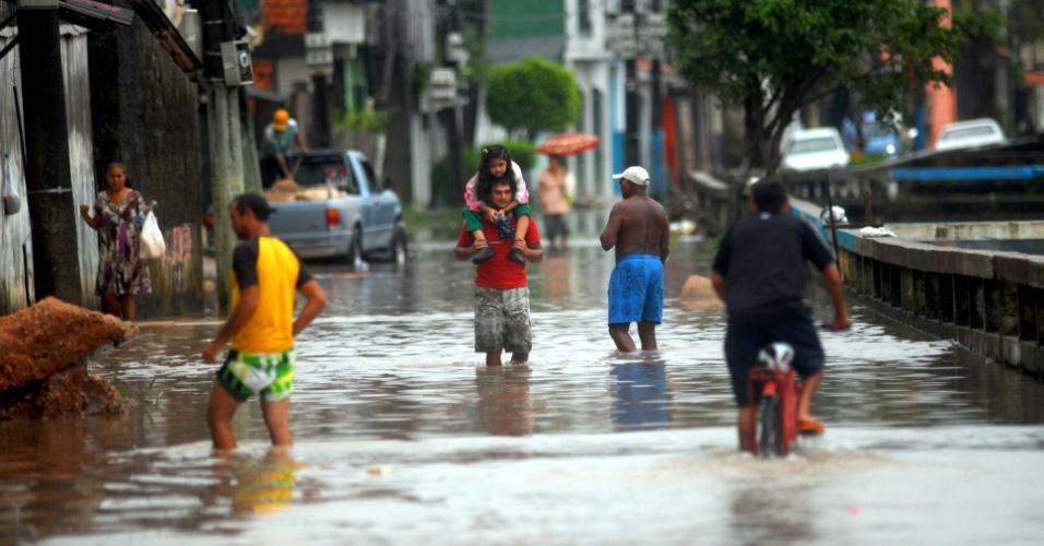 Moradores tentam passar por rua alagada do bairro do Marco, em Belém (PA)