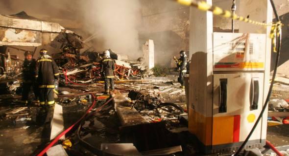 17.jul.2007 - Bombeiros avaliam os estragos em posto de gasolina atingido pelo avião