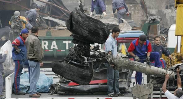 18.jul.2007 - Bombeiros e operários retiram destroços do avião