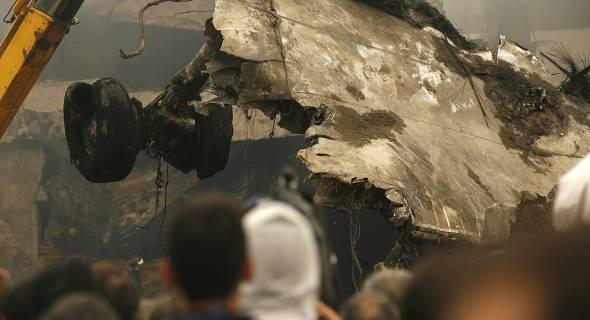 18.jul.2007 - Curiosos observam retirada dos restos do avião