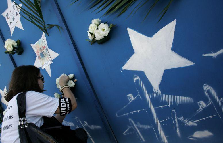 17.jul.2008 - Mulher homenageia familar morto na queda do Airbus da TAM