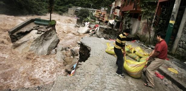 Turistas ajudam a fazer barragem improvisada em Aguas Calientes, no Peru