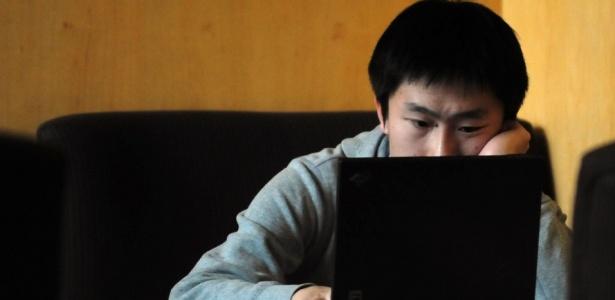 Jovem navega na web em um café com acesso à internet em Pequim, na China