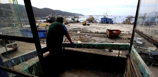 Homem observa destruição causada pelo terremoto em Talcahuano (Chile)