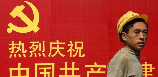 Trabalhador passa diante de cartaz do congresso do Partido Comunista