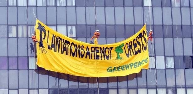 Ativistas do Greenpeace penduram bandeira de protesto gigante na lateral do edifício-sede do governo de Jacarta, na Indonésia