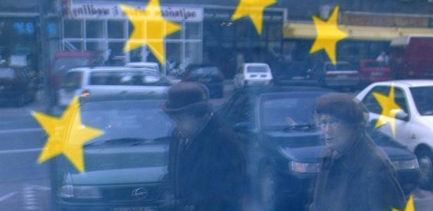 Polonesas têm sua imagem refletida em janela de escritório da União Européia em Varsóvia, Polônia