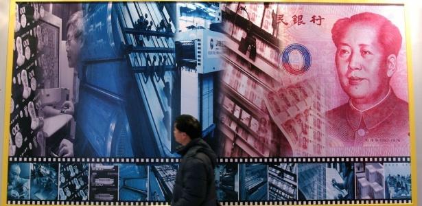 Visitante passa diante do pôster que mostra o processo de desenho e impressão da moeda chinesa, o yuan, durante exposição no Museu Nacional da China, em Pequim