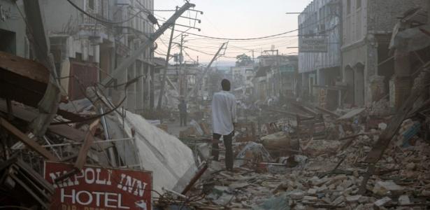 Homem caminha desolado pelos destroços do terremoto que atingiu a capital do Haiti, Porto Príncipe