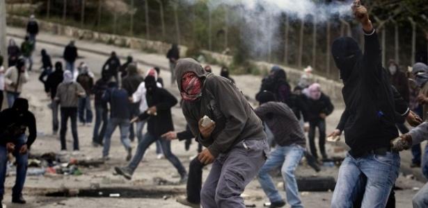 Manifestantes palestinos atiram pedras contra a polícia israelense em Jerusalém Oriental. O grupo islâmico palestino Hamas convocou um Dia da Ira para protestar contra as ocupações