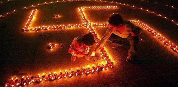 Crianças brincam com o símbolo da suástica formado por velas no Paquistão, que considera a imagem um símbolo religioso de boa sorte