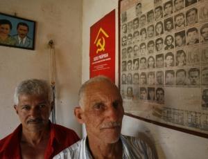 O lavrador José Rodrigues da Silva (à frente) com José Nazário, em São Geraldo do Araguaia (PA), à frente de quadro com fotos de desaparecidos durante os confrontos com militares