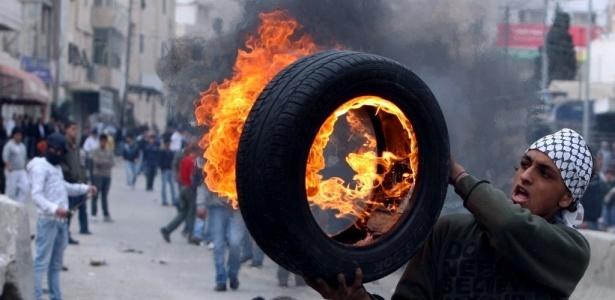 Jovem palestino se prepara para lançar um pneu em chamas durante confrontos com forças israelenses no campo de refugiados de Kalandia, entre Ramallah e Jerusalém