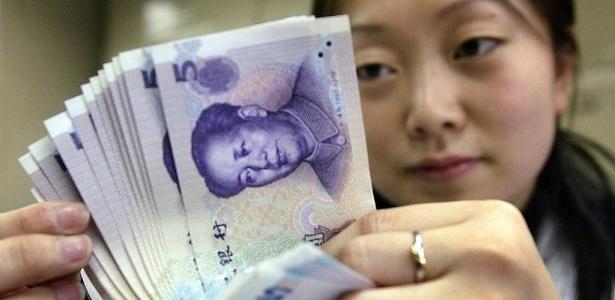 Funcionária do Banco da China confere cédulas de yuan em Pequim, capital do país