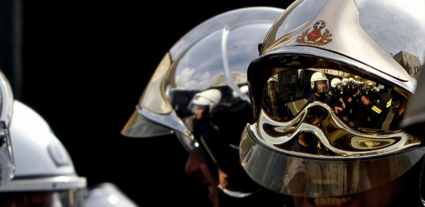Reflexo em capacete de bombeiro mostra policiais alinhados em frente ao parlamento grego durante protesto contra o governo, em Atenas