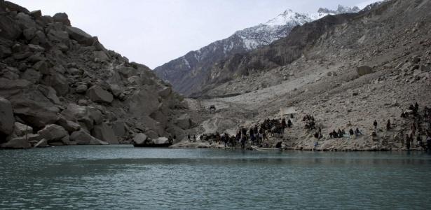 Pessoas esperam barco para cruzar o lago criado por um deslizamento de terra na região de Attabad, no norte do Paquistão; rompimento de barragem pode criar ondas de 20 m de altura