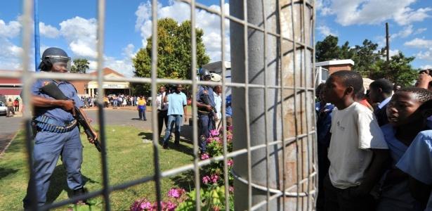 Policial sul-africano olha crianças que protestam contra a morte de quatro pessoas atropeladas pelo rapper Jub Jub