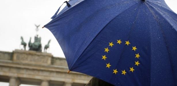 Homem com guarda-chuva com o logotipo da União Europeia, em Berlim (Alemanha)