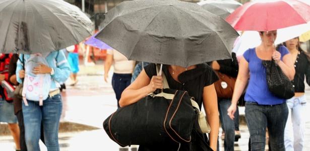 Pedestres usam guarda-chuvas na avenida Faria Lima, em São Paulo, na tarde desta sexta-feira (26); capital paulista entra em estado de atenção devido à chuva