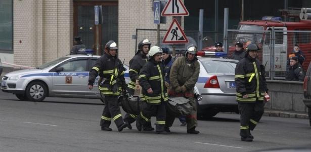 Bombeiros transportam corpo de uma das vítimas dos atentados no centro de Moscou. Duas explosões atingiram o sistema de metrô da cidade durante a manhã de segunda-feira (29)