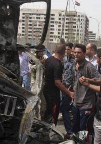 Iraquianos observam carro-bomba utilizado em atentado em Bagdá