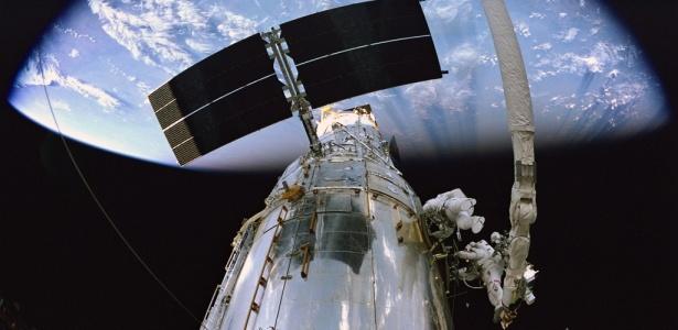 """Em uma cena do """"Hubble 3D"""", os astronautas Andrew J. Feustel (direita), e John M. Grunsfeld, fazem reparos no Telescópio Espacial Hubble"""