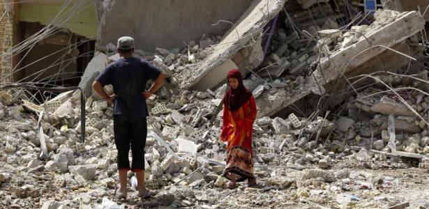 Pessoas caminham sobre os escombros e procuram vítimas dos ataques em Bagdá (Iraque)