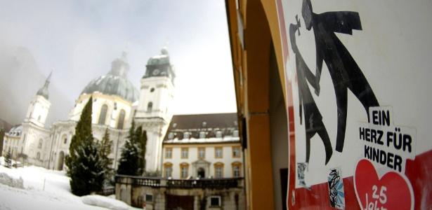 Adesivo que diz um coração para as crianças é colado em placa ao lado da igreja do Mosteiro de Ettal, ao sul de Munique, na Alemanha