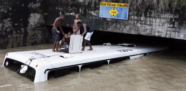 Jovens brincam em ônibus coberto pela água no bairro do Jacaré, no Rio - Marcos Tristão/Agência O Globo