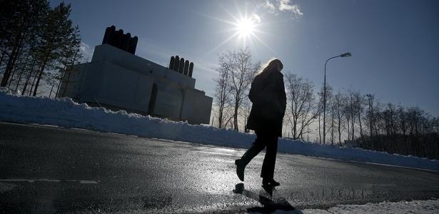 Uma mulher caminha em frente de instalação de resíduos nucleares, em Osthammar, na Suécia