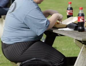 Homem obeso almoça tomando refrigerante; bebidas açucaradas representam 7% das calorias que os norte-americanos consomem diariamente