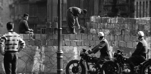 """Homem trabalha na construção do muro de Berlim; estudo revela que russos planejaram a construção de um grande """"bunker"""" pensando em uma possível guerra contra o ocidente"""