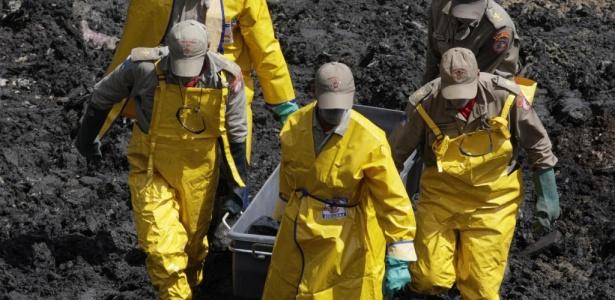 Bombeiros carregam o corpo de mais uma vítima do desabamento no morro do Bumba