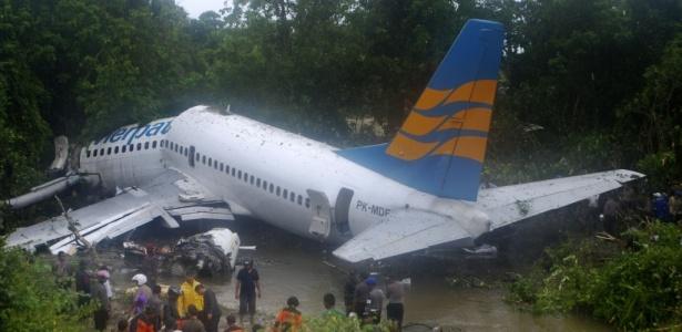 Homens trabalham em resgate ao lado dos destroços do Boeing 737 da Merpati Nusantara Airlines depois de um acidente no aeroporto de Rendani, em Manokwari (Indonésia)