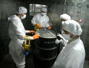 Técnicos manuseiam barril de 'yellow cake' (urânio ainda não enriquecido)