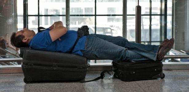 Passageiro repousa sobre suas malas no aeroporto de Fiumicino, perto de Roma, na Itália