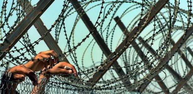 Iraque Sob Tutela: prisioneiros iraquianos observam grupo de presos libertados que estava saindo da prisão de Abu Ghraib, nos arredores de Bagdá