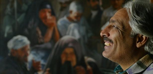 O artista iraquiano Qasim Sabti sorri em frente a uma de suas obras em um café em Bagdá