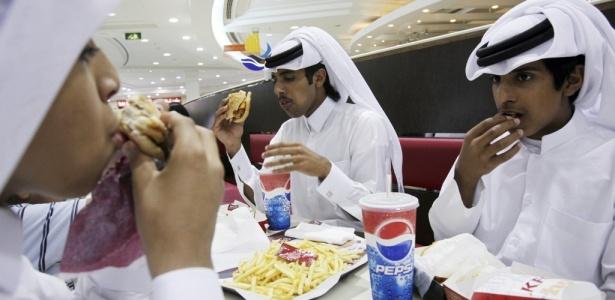 Jovens do Qatar comem em um fastfood na cidade de Doha. A pequena nação do Golfo Pérsico está entre os líderes do mundo em casos de obesidade e diabetes