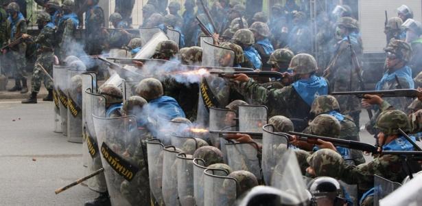 """Tropa de choque da polícia tailandesa atira contra """"camisas vermelhas"""" em Bancoc, durante manifestação na semana passada. Acordo com governo colocou fim aos protestos no país"""