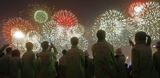 Voluntários assistem ao show de fogos de artifício na cerimônia de abertura da Expo Xangai